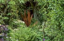 Ferns, rusty metal sculpture in border, willow