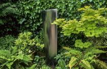 Water feature by Simon Percival in border, ferns, ivy, Acer palmatum 'Aureum'