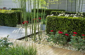 Yew hedges, bamboo, peonies, fencing, limestone mulch, decking
