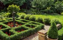Square box knot on brick terrace, red pelargoniums, human figure statue, box cones in pots, box balls, lawn