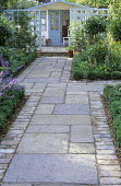Stone path to summerhouse, standard bay trees, pale blue-painted trellis screens