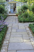Stone path to summerhouse, standard bay trees, pale blue-painted trellis screens, box edging