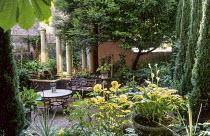 Cupressus sempervirens, brick beds, urn fountain, columns, table, chairs, bench, mirror, hostas, ferns, trellis