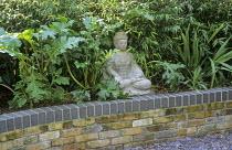 Buddha in brick raised bed, acanthus, Phyllostachys nigra