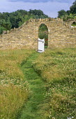 Archway in stone wall, white gate, curving mown path cut through clover meadow
