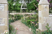 Stone piers by enclosed garden entrance, irises