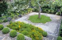 Stone paved terrace, box balls, beds with Santolina rosmarinifolia subsp. rosmarinifolia, pebble mosaic by Michael Gough, apple tree, pond