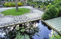 Rectangular pond, pebble mosaic by Michael Gough, apple tree in lawn, tiles by Delphina Bottacini, Aponogeton distachyos