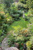 View from above of town garden, lawn with stone urn, borders in late summer patio with table and chairs