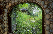 Framed view from shell grotto over pond to summerhouse, shellwork wall