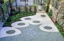 Contemporary urban courtyard, pebble mosaic, ceramic tiles, trellis screen fencing, wall water feature