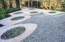 Contemporary urban courtyard, pebble mosaic, wooden bench, Echeveria elegans