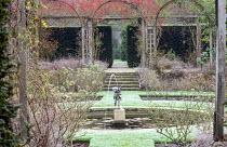 Circular fountain in sunken rose garden, rosehips, yew hedges