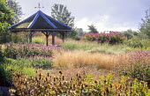 View over Millenium garden to pavilion, Deschampsia cespitosa 'Goldtau', Persicaria amplexicaulis 'Rosea', Monarda 'Mohawk', eupatorium