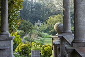 View from stone portico, clipped Buxus sempervirens, euphorbia