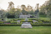 Sundial in formal box-edged parterre, stone wall, tulips