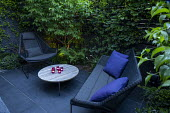 Contemporary chairs on black paving, candles on table, uplit stems