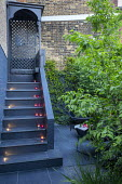 Candles on black steps, contemporary chairs in shady courtyard