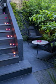 Candles on steps, contemporary chairs on black paving