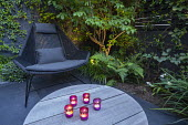 Contemporary chair on black paving, candles on table, uplit stems