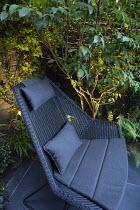 Contemporary chair on black paving, uplit stems