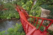 Red painted walkway bridge, waterfall, Adiantum raddianum 'Fragrantissimum', Araucaria araucana, Lophosoria quadripinnata, Buddleja globosa, Valeriana officinalis