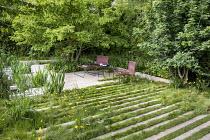 Contemporary chairs on stone and grass terrace, Iris pseudacorus, Acer campestre, Carpinus betulus, Ranunculus acris