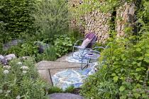 Chairs on concrete terrace, Valeriana officinalis, Lamium orvala, cut log wall, Salix purpurea 'Nancy Saunders'