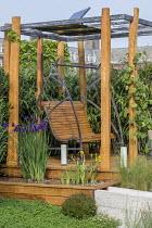 Metal and wood swing bench in pergola, Iris laevigata and Iris pseudacorus in raised pond