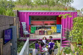 Re-purposed shipping container as garden pavilion, metal railings, gravel terrace