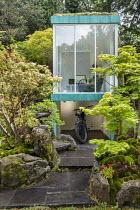 Japanese garden, large rocks, Enkianthus campanulatus, Acer palmatum, Pinus mugo, chair in glazed garden room, motorbike