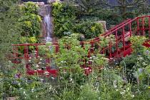 Waterfall over stone wall, red walkway, Valeriana officialis, Sambucus nigra