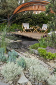 Deckchairs on wooden decking overhanging pool, orange fabric awning, slabs of Caithness stone