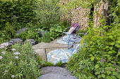 Chairs on concrete terrace, Valeriana officinalis, Lamium orvala, cut log wall, salix