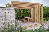Wooden table and benches under contemporary pergola, stone wall and patio, stone-edged stream, Valeriana officinalis, hornbeam hedge