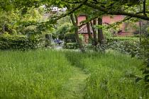 Mown grass path through long grass meadow