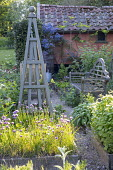 Wooden bench in herb garden, wooden obelisks, Salvia officinalis, rosemary, chives, mint