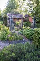 Wooden bench in herb garden, wooden obelisks, Salvia officinalis, Allium schoenoprasum, mint, rosemary, lavender