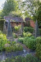 Wooden bench in herb garden, wooden obelisks, Salvia officinalis, Allium schoenoprasum, mint, rosemary