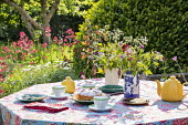 Teapot, cups and cake on table, vase of cut flowers, afternoon tea, tablecloth, Centranthus ruber