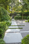 Limestone path across gravel terrace, clipped Taxus baccata, Thymus serpyllum rills, view to urn on plinth, Rodgersia aesculifolia