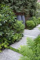 Side passage, gravel path, Hebe parviflora var. angustifolia, Pittosporum tobira, Trachelospermum jasminoides climbing on house wall, hellebore, Dryopteris filix-mas, Elaeagnus x ebbingei
