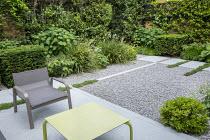 Contemporary chair and table on stone patio, white gravel, clipped yew hedges, Thymus serpyllum rills, Pittosporum tobira 'Nanum', Libertia grandiflora, Hydrangea arborescens 'Annabelle'