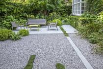 Contemporary chairs and table on stone patio, white gravel, clipped yew hedges, Thymus serpyllum rills, Pittosporum tobira 'Nanum', euphorbia, Alchemilla mollis, Libertia grandiflora