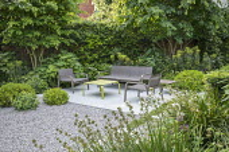 Contemporary chairs and table on limestone patio, white gravel, clipped yew hedges, Pittosporum tobira 'Nanum', Euphorbia characias subsp. characias 'Humpty Dumpty', Alchemilla mollis, Libertia grandi...