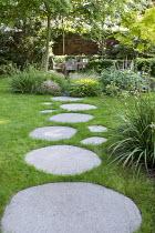 Circular stepping stone path across lawn leading to seating area, Libertia grandiflora, Acer palmatum, Hakonechloa macra, Saxifraga umbrosa