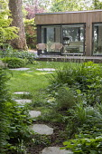 Stepping stone path across lawn, Hakonechloa macra, Libertia grandiflora, chairs on terrace by contemporary pavilion