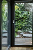 View from inside pavilion through glass door to Fatsia japonica outside