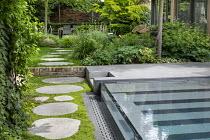 Stepping stone path by contemporary infinity swimming pool, Soleirolia soleirolii, pavilion, Aruncus 'Horatio', Helleborus argutifolius, Geranium nodosum 'Clos du Coudray'