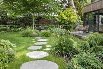 Stepping stone path across lawn leading to seating area, Libertia grandiflora, Hakonechloa macra, Saxifraga umbrosa, Geranium nodosum 'Clos du Coudray', Acer palmatum